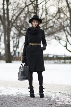 snow outfits, what to wear in a snowstorm, winter outfit, all black-black tights-winter work outfit-blakck coat-black coat-gloves-velcro boots-black tote-gold belt-belted coat-wide brim hat-winter style-what to wear when its freezing outside-snow outfit-