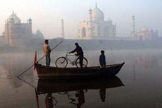"""A man travels on a small boat with his bicycle along the Yamuna river near the Taj Mahal in Agra, India"""