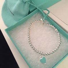 "Tiffany & Co. Return to Tiffany bead bracelet Size small, 6.5 inches bracelet length, beads are 4 mm, one side of the heart is the Tiffany blue, the other side is the classic ""please return to Tiffany & co."" It does have two beads that look a little smushed, it came like that! It is not noticeable when wearing. Only been worn a handful of times, recently professional cleaned by Tiffany and co! Like new! Comes with box, jewelry bag, Tiffany ribbon, and Tiffany paper bag! Tiffany & Co. Jewelry…"