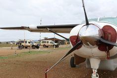 En Cessna Caravan på Serengetis flygfält i Tanzania med Jambo Tours safarifordon i bakgrunden