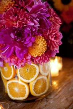 Colorful flowers in clear vase with cut oranges.