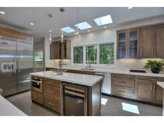 A modern and spacious kitchen with hardwood cabinets, natural lighting, and top of the line stainless steel appliances. Palo Alto, CA Coldwell Banker Residential Brokerage