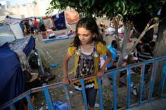 A Palestinian girl, who fled the Israeli ground offensive and air strikes, stands near makeshift tents in the garden of the Shifa hospital in Gaza City, July 31, 2014.