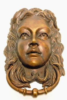 A large bronze Door Knocker in the form of a young woman's face with cascading hair.                                                                                                                                                                                 More
