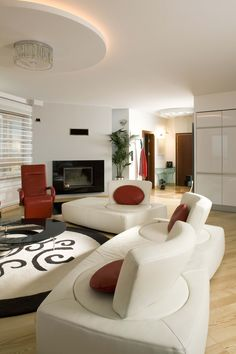 White and natural wood living room holds a pair of ultra-modern sofas with rotating seats around a circular patterned rug and ring-shaped coffee table. Deep red armchair is matched by decorative sofa pillows.