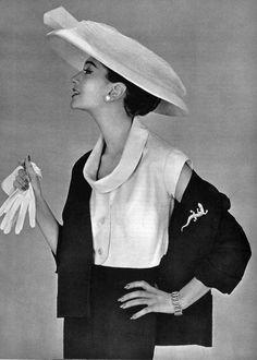 Model in white bolero worn under a black woolen jacket by Lanvin-Castillo, hat by Legroux, jewelry by Marcasite, photo by Philippe Pottier, 1956