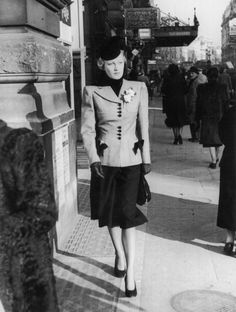 London c1940: A smartly dressed woman walks down a London street. Her tailored suit has squared shoulders and the contrasting buttons and trim on her jacket match the 'just below the knee' skirt. Original Publication: Picture Post - 370 - A Pretty Girl Goes for a Walk - unpu ~
