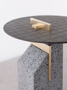Formafantasma furniture made from Mount Etna Lava / here 'Modest Pillar' table - materials, basalt, Occhio di pernice basalt, brass, textile.