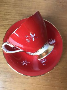 H & M Sutherland Vintage Teacup and Saucer (Hudson and Middleton) This is a stunning bright red teacup and saucer. This shiny set has different little white flowers hand painted around the cup and saucer. Inside the cup is a grey and red outline of leaves. This set is trimmed in gold on