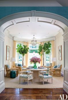 The solarium is furnished with Bielecky Brothers rattan lounge chairs and John Rosselli & Assoc. benches, all cushioned in a Quadrille linen.