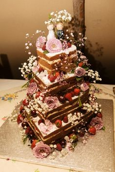 A rustic  rustic heart-shaped naked cake decorated with edible flowers and fruit - real weddings
