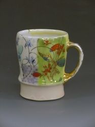 In this mug, Jennifer Allen is completely throwing out all of the norms of surface decoration. She is layering different patterns, but maintains a level of harmony on the surfaces, and how these patterns move around the form. The cup is now well used, leading to its cracked status and luster wearing off the handle. Her pottery was influential in the decorative pottery movement of the early 2000's.