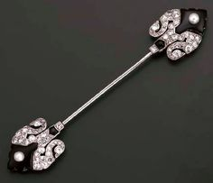AN ART DECO ONYX, DIAMOND AND PEARL JABOT PIN, BY CARTIER  Each terminal with an onyx, pearl and openwork diamond arrowhead shaped panel, circa 1925, 8.8 cm. wide, with French assay mark for platinum Signed Cartier Paris