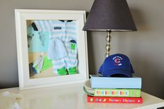 Shadow box with going home from the hospital outfit and other keepsakes - love this displayed in the nursery! #nursery #keepsakes