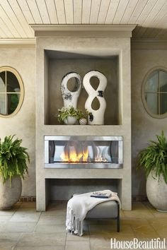 A gas-powered outdoor fireplace warms theloggia off an Atlanta home'sgreat room on crisp autumn evenings. The Ballard Designs planters are modeled on olive-oil jars.