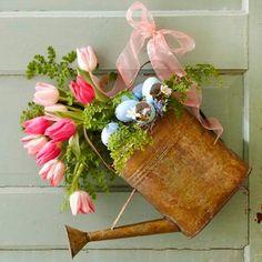 un arrosoir avec des tulipes et plantes vertes accroché à la porte