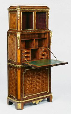 "1775 French Secrétaire (shown open) at the J. Paul Getty Museum, Los Angeles - From the curators' comments: ""This secrétaire provided its owner with a display area fitted with glass doors at the top, a writing surface with pigeonholes concealed behind the fall front, and a storage cupboard at the bottom. The delicate, quatrefoil-patterned marquetry with mother-of-pearl inlay and the gilt bronze floral swags mounted at the top of the fall front soften its sharply rectilinear form."""
