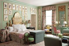 The heirloom headboard in the master bedroom is surrounded by 19th-century bird portraits by Hannah Pettigrew; a printed cotton from Claremont is used throughout, and at the foot of the bed is a cabinet, upholstered in an Old World Weavers velvet, that contains a television; the needlepoint rug is by Stark.