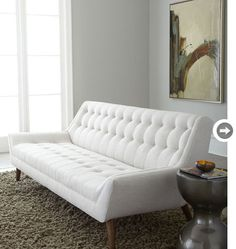 Mad Men-inspired decor: Tufted sofa  With all the wood accessories and rich brown hues used during the period, it's nice to contrast with a lighter piece. This Jonathan Adler tufted sofa has the classic mid-century modern shape, but takes a contemporary turn by using white fabric.