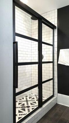From Coastal Shower Doors, the Gridscapes series of true divided-light windowpane sliding shower doors. Shown here, framing white subway tiles with black grout and a geometric tile floor.