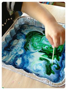 Milk, food coloring, and a toothpick dipped in dish soap.