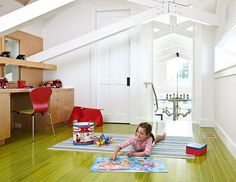 A green-stained ash floor provides unique color underfoot in the lofted playroom. - Traditional Home ®/ Photo: Werner Straube