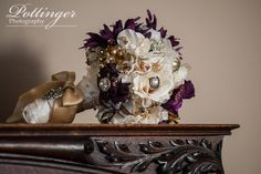 We love this broach bridal bouquet. The purple, ivory and gold colors are such a great vintage accent. Photo by Pottinger Photography www.pottingerphoto.com
