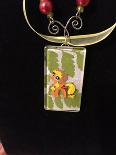 Inspired by My Little Pony!  I am such a huge MLP fan, and I love multi-media projects!  Necklace incorporates wire charms (hand-bent) inspired by Applejacks Cutie Mark- in this case apples, and is finished with a ribbon accent.  Beads are on hand-bent wire and are inspired by Applejacks coloring.  The charm has a paper background Mod-Podged onto an acrylic charm, filed down at edges to discourage peeling. Each pony is hand-painted by yours truly!  Necklace is approximately 20 inches long…
