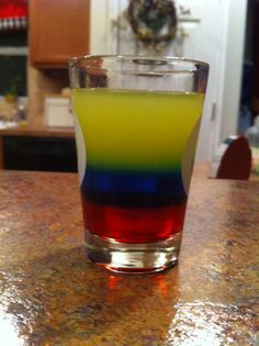 Colombia Shot! Ingredients: Grenadine, Bols Blue Curacao, Smirnoff Vodka 80 Proof, Orange Juice, Lemon Juice Mix the lemon and orange juice together with Aguardiente/Vodka and ice. Layer in a shot glass in this order: 1st. Grenadine 2nd. Blue Curaçao. (on top) 3rd. The mix you made for the yellow. Voila !!!! You have our flag!!