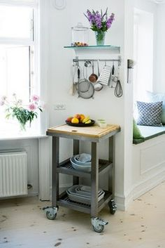 small rolling island. perfect for a tiny kitchen....and you can make it short enough to roll right under the dining table