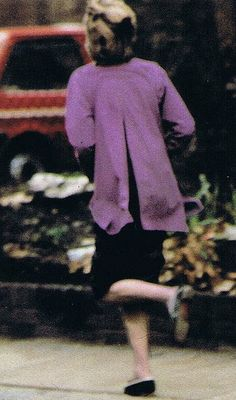 November 23, 1980: Lady Diana Spencer trying to get away from annoying photographers. Wearing a purple sweater.