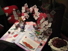 """Detail from Tablescape for """"Mad Hatter Tea Party"""" featuring a pop-up """"Alice In Wonderland"""" book as guest favors."""
