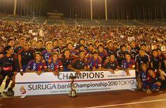 [ スルガ銀行チャンピオンシップ 2010 TOKYO F東京 vs リガ・デ・キト ] サポーター・ファンをバックに記念撮影をするFC東京の選手とスタッフ。クラブ史上初の国際タイトルを獲得するとともに日本勢として初めてスルガ銀行チャンピオンシップのタイトルを獲得した。  2010年8月4日(水):国立競技場