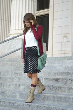 White top, maroon cardigan, black and white polka dot skirt, maroon socks, tan lace-up boots