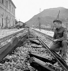 Sergeant F.H.J. Ricketts examining railway ties which were cut by the last German train through Carovilli, Italy, 26 November 1943