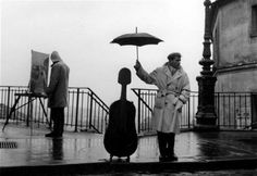 A man on the sidewalk in rainy Paris. The man uses his umbrella to protect his cello case. This is the famous cellist Maurice Baquet. The image was taken by photographer Robert Doisneau in Robert Doisneau, White Picture, Black White Photos, Black And White Photography, Vintage Photography, Street Photography, Art Photography, Famous Photography, Maurice Baquet