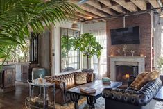 Leather sofas, greenery and an old brick wall ... exposed beams. Fireplace. LOVE.