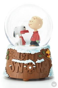 """Bring the charming duo of Snoopy and Charlie Brown into your home this holiday season with this festive """"Let it Snow"""" Peanuts snow globe from Hallmark. This Christmas decoration would look great on a winter-themed fireplace mantel."""