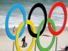 A vendor sells sunglass as a woman jogs and a sunbather lays out on Copacabana beach as the Olympic rings rise from the beach volleyball arena at the 2016 Summer Olympics in Rio de Janeiro, Brazil, Monday, Aug. 8, 2016. (AP Photo/David Goldman)