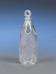 This delicate glass perfume bottle was created by the famed René Lalique. Crafted in the highly desirable Palermes pattern, this delicate perfume features an elegant design of pearl garlands, and is a superb example of Lalique's clean and sophisticated Art Deco style. Lalique's perfume bottles are among the most desirable items with collectors. He first began to design them at the request of his neighbor, legendary parfumier François Coty, who greatly admired Lalique's designs. In 1907, Coty…