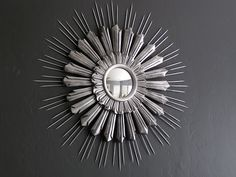 diy enhanced sunburst mirror (i.e. she bought it and then enhanced it with bamboo skewers and spray paint)