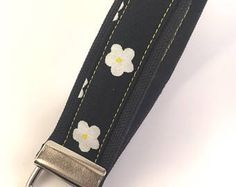 Black canvas keyfob with daisy print. Girly without being over the top.
