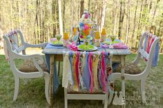 Fun Easter table setting.  Bright colors perfect for brunch or children's party.  Brightly colored fabric is tied to the back of each chair.  The centerpiece is a glass jar cloche filled with brightly colored Easter eggs.  Pink, green blue, white.  Very shabby cottage