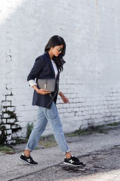 Try a pair of mirrored sunglasses, a white longsleeve top layered under a black blazer, and a cuffed boyfriend jean back to New Balance sneakers and a Saint Laurent shoulder bag.