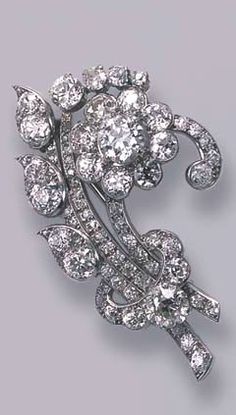 A DIAMOND FLORAL SPRAY BROOCH, BY CARTIER  Designed as an old-cut diamond floral cluster with three diamond stems and paisley-shaped leaves to the graduated diamond tie, circa 1930, 5.1 cm. wide, in original Cartier red leather fitted case Signed Cartier London