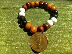 Plumeria Elizabeth Bracelet Wood beads and charm  Like us on https://www.facebook.com/plumeriajewelry to see our pieces.