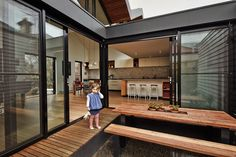 The architects pulled away the roof at the house's center to create a courtyard where the residents can enjoy meals. The ground sits below floor level, which means that the wraparound eucalyptus deck can also serve as a bench.