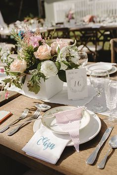 Wooden tables set with mismatched vintage china and mixed arrangements of pink, white, and peach roses | Brides.com