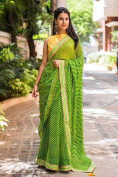 It's pouring chic leheriyas with bewitching details this monsoon! These easy breezy drapes with vibrant and colourful wave patterns are making their appearance once again…Don't miss the gold filigree border detailing in this fresh green yellow leheriya drape.Go yellow for the blouse for maximum appeal. Or strike out with a chic black blouse for another kind of a style statement. #green #yellow #georgette #leheriya #saree #India #blouse #houseofblouse