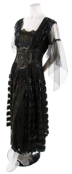 A Black Tulle and Sequin Dress,  circa 1920,  with tulle sleeves, sequined striped straps, hand beading across waist with tambouring at center with beaded fringe, tulle and sequined striped skirt. Labeled: B. Altman & Co./New York/Paris.